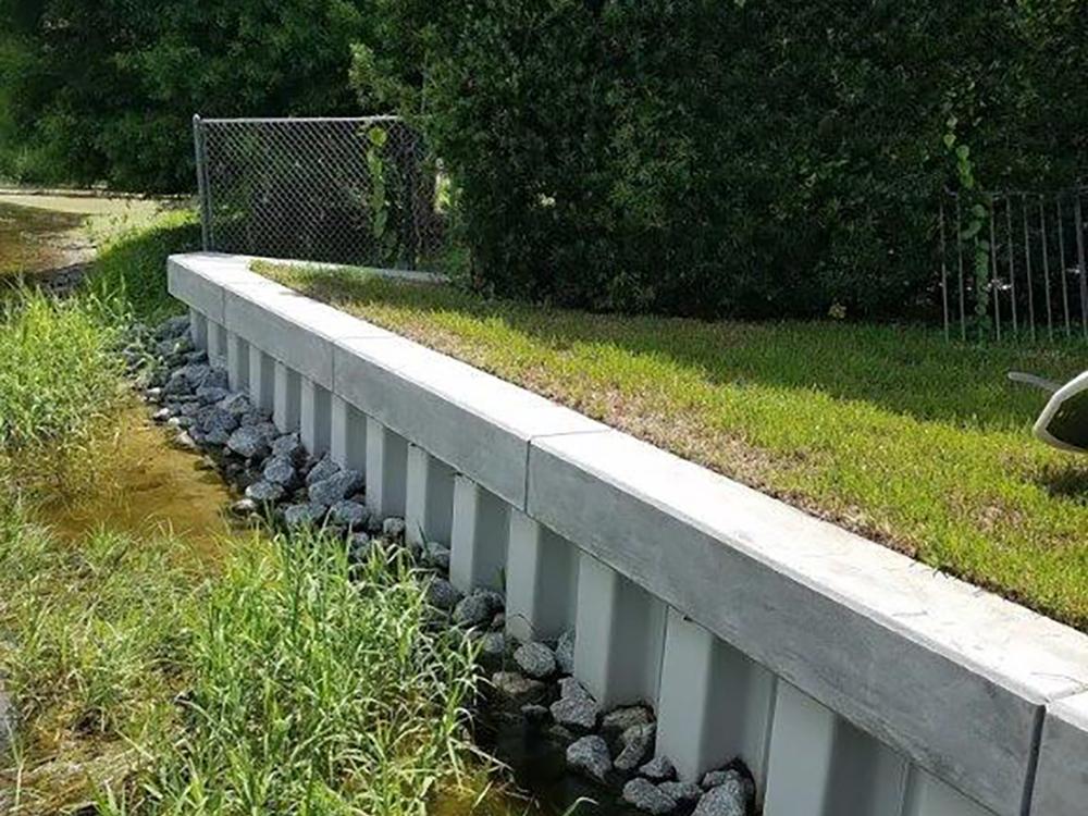 Vinyl seawall with concrete cap and stone revetment in Orlando